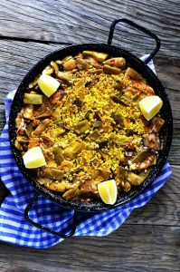 veggie paella in a black pan on a wooden table