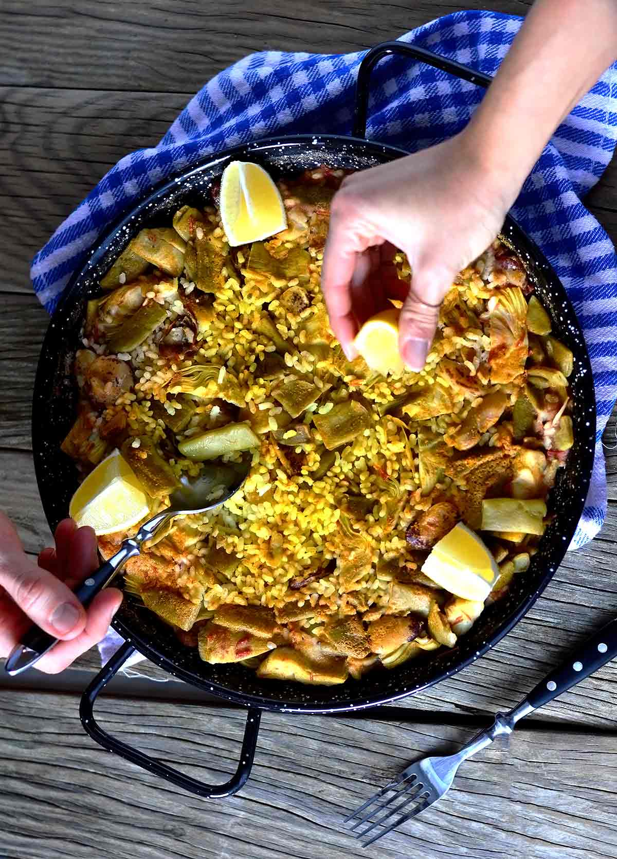 Two people eating from a paella in a pan