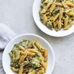 two plates of spinach and mushroom pasta