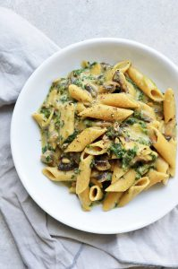 spinach and mushroom pasta served on a white plate