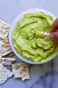 creamy avocado dip on a white bowl