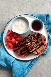 Strawberry and oatmeal pancakes served with maple syrup, yogurt and chopped strawberries