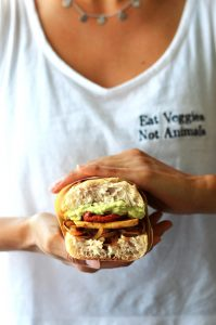 holding this delicious hearty vegan tofu sandwich
