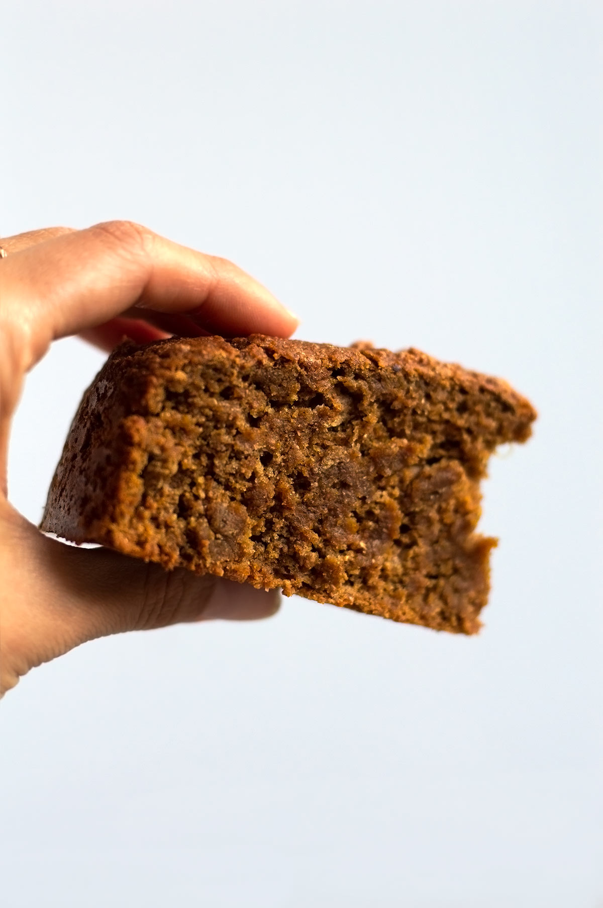 holding a piece of pumpkin bread